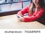 woman in red coat sitting in...   Shutterstock . vector #742689895