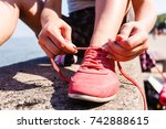 Small photo of Outdoor relax holidays nature concept. Young girl tying shoelace. Lady sunbathing on coast making a knot.