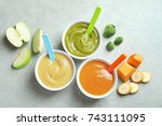 bowls with baby food on grey... | Shutterstock . vector #743111095