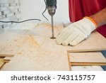 the man drills the hole in the... | Shutterstock . vector #743115757