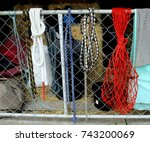 Small photo of close-up of colorful horse ropes and empty hay net on my stable gate; unstaged and rustic, showing hay bales in background