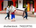 Small photo of SIKKIM, INDIA - MAR 13, 2017: Unidentified Indian men carry unknown object along the street and one man aslo carries a basin on his head.