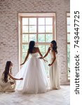 Small photo of Making sure she looks perfect. Full length of bridesmaids helping bride with her wedding dress while standing near the window together