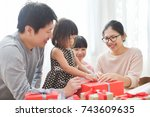 happy asian family wrapping a...   Shutterstock . vector #743609635