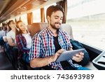 Small photo of The guy in the shirt sits on the bus and looks at something on his gray tablet. He smiles. Behind him sit other tourists who go on a journey.