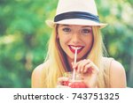 young woman drinking a smoothie ... | Shutterstock . vector #743751325