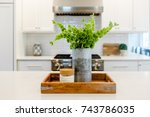 Small photo of wooden accent tray with silver tin of green flowers in a white kitchen