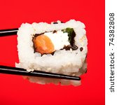 Salmon and cream cheese sushi roll being held in chopsticks. Photographed against a red studio background. - stock photo