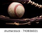 Old scuffed baseball sitting inside a brown leather glove. - stock photo
