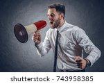 businessman screaming into a... | Shutterstock . vector #743958385