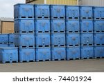 Stacks of bright blue industrial shipping containers outside a fish processing company near the docks - stock photo