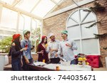 Small photo of Cheers to best friends! Top view of cheerful young people cheering with champagne flutes and looking happy while having party on the kitchen ,celebrating Christmas or New Year at home