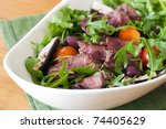 Salad with rare sliced beef, arugula, mushrooms, cherry tomatoes and carrots.  Simple, delicious eating. - stock photo