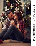 Small photo of Young husband hugging and kisses his wife while gives her Christmas present