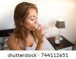 woman drinking water in bedroom | Shutterstock . vector #744112651