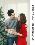 christmas asian couple. a... | Shutterstock . vector #744124585