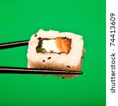 Salmon and cream cheese sushi roll being held in chopsticks. Photographed against a white  studio background. - stock photo