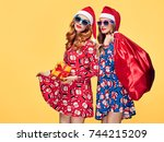 christmas. two young woman and... | Shutterstock . vector #744215209