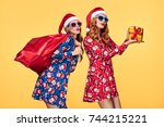 christmas. two young woman and... | Shutterstock . vector #744215221