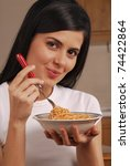 young woman eating cereal corn. | Shutterstock . vector #74422864