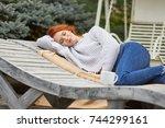 woman relaxing on a wooden...   Shutterstock . vector #744299161