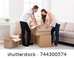 young couple unpacking moving... | Shutterstock . vector #744300574