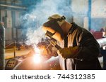 sparks while welder uses torch... | Shutterstock . vector #744312385