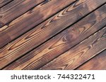 Small photo of Structure of the scorched wood. Wooden boards are adored with fire.
