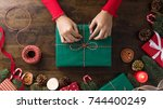 woman in a red sweater wrapping ... | Shutterstock . vector #744400249