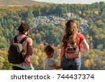 young family looking at fall colors from top of west bluff at Devils lake state park in Wisconsin