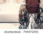 Small photo of Close-up old wheelchair in front of the Outpatient Department of Hospital with sunlight