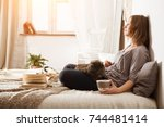 young woman with a cat  lying... | Shutterstock . vector #744481414