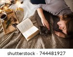 Stock photo young woman with a cat lying in bed at home winter or autumn weekend concept 744481927