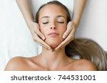 young blond woman receiving a... | Shutterstock . vector #744531001