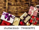 Small photo of From above shot of beautifully wrapped giftboxes adorned with ribbons and stacked on wooden background.
