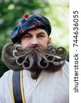Small photo of Close-up portrait of a brave Scot with a amazing beard and mustache curls . Checkered red Scottish kilt skirt, hat with pompon, cane and sword. Beard styling by professional barbershop.