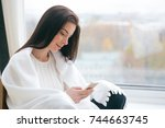 woman with mobile phone at home ... | Shutterstock . vector #744663745