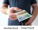 man handing out ten dollar... | Shutterstock . vector #744675529