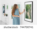 young woman looking at picture... | Shutterstock . vector #744700741
