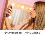 beautiful young woman applying... | Shutterstock . vector #744728551