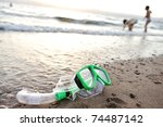 Snorkeling mask on the beach, children playing around - stock photo