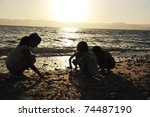 Group of children playing in sand before sunset - stock photo