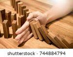 businessman hand stop dominoes... | Shutterstock . vector #744884794