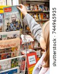 Small photo of STRASBOURG, FRANCE - OCT 28, 2017: Woman buying The Economist magazine at press kiosk featuring Vladimir Putin on cover and headline A Tsar is Born