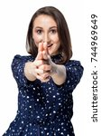 Pretty young happy smiling girl making gun gesture and pointing at camera on white background