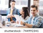 smiling man holding a sheet of... | Shutterstock . vector #744992341