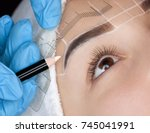 Small photo of Permanent make-up for eyebrows of beautiful woman with thick brows in beauty salon. Closeup beautician doing tattooing eyebrow.
