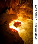 "Small photo of Underground cave with stunning ""island of fire"" in a pool at Marakoopa Caves in Tasmania"