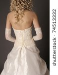 Back of bride in wedding dress on a gray background. - stock photo