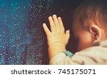 baby looking through rainy... | Shutterstock . vector #745175071